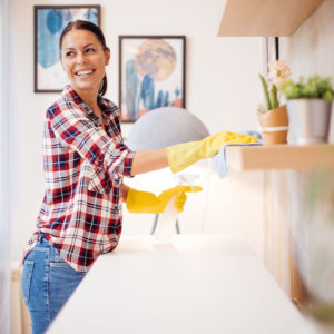 woman cleaning shelves in cabin rental