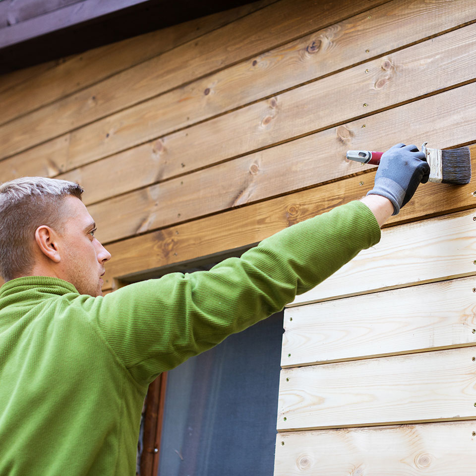 man painting exterior of cabin
