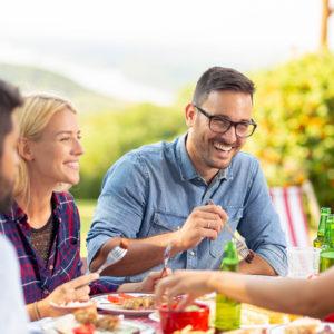 smiling guests eating dinner outside cabin